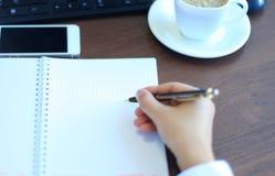 Il primo piano della donna di affari fa una nota Immagine Stock