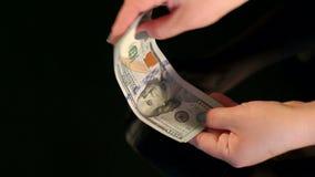 Il primo piano della donna di affari piega una pila di dollari archivi video