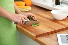 Il primo piano della donna passa la cottura delle verdure insalata in cucina Concetto sano del vegetariano e del pasto fotografia stock