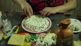 Il primo piano della donna passa la preparazione e decorato con insalata di verdure nella cucina video d archivio