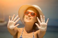 Il primo piano della femmina con le mani aperte ha ricoperto di crema d'abbronzatura fotografia stock libera da diritti