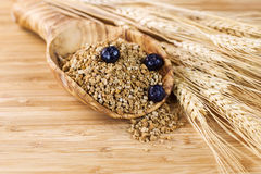 Intero cereale naturale del grano in cucchiaio di legno Fotografie Stock