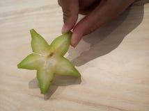 Il primo piano della frutta di stella tiene dalle dita fotografia stock libera da diritti