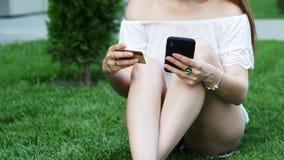 Il primo piano della giovane donna fa gli acquisti online facendo uso del telefono, entra in una seduta del numero di carta di cr video d archivio