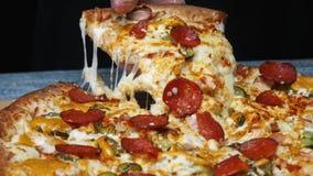 Il primo piano della mano del cuoco unico in guanto protettivo che prende un pezzo di pizza delizioso con salame, marina il forma stock footage