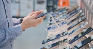 Il primo piano della mano di un uomo gira ed ispeziona la progettazione di nuovo smartphone in un deposito moderno di elettronica archivi video