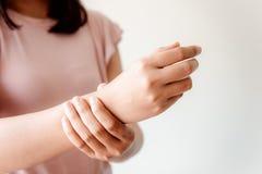 Il primo piano della mano della donna sta massaggiando il suo dolore del polso da compito Malattia del muscolo e concetto di sind immagini stock