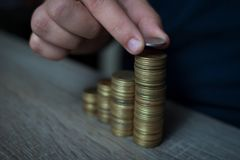 Il primo piano della mano ha messo le monete alla pila di monete, soldi di risparmio di concetto Fotografia Stock Libera da Diritti