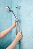 Il primo piano della mano umana regola la testa di doccia del supporto di altezza Immagine Stock