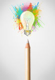 Il primo piano della matita con pittura colorata spruzza e lampadina Immagine Stock