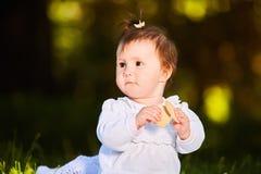 Il primo piano della neonata sveglia che si siede nel parco e mangia lo spuntino al giorno caldo Fotografie Stock