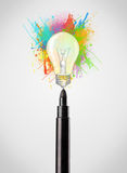 Il primo piano della penna del feltro con pittura colorata spruzza e lampadina Immagine Stock Libera da Diritti