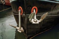 Il primo piano della prora e l'ancora arrugginita di una barca hanno attraccato in porto a Amsterdam immagini stock