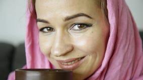 Il primo piano della ragazza musulmana nel hijab rosa beve il caffè video d archivio