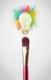 Il primo piano della spazzola con pittura colorata spruzza e lampadina Fotografia Stock