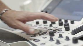 Il primo piano della tastiera di ultrasuono, mani di medico clicca sopra il bottone video d archivio