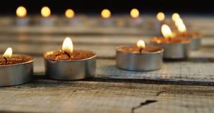 Il primo piano delle candele brucianti ha tenuto nella fila sulla plancia di legno video d archivio