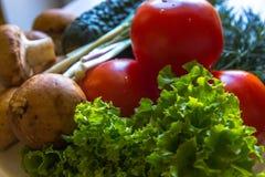 Il primo piano delle foglie dell'insalata, i pomodori ed i cetrioli freschi su bianco kithen Fotografia Stock Libera da Diritti