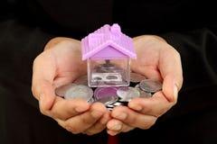Il primo piano delle mani che tengono le monete e la casa modellano Fotografia Stock Libera da Diritti