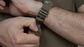 Il primo piano delle mani degli uomini in vestiti cachi, è rimosso dall'orologio sulla cinghia di nylon archivi video