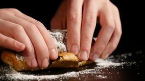 Il primo piano delle mani del ` una s dell'uomo rompe un croissant fresco Pasticcerie dolci fresche, primo piano video d archivio