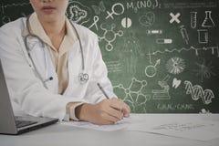 Il primo piano delle mani di medico scrive su carta Fotografia Stock Libera da Diritti
