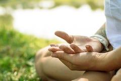 Il primo piano delle mani femminili ha messo in mudra di yoga La donna meditating Fotografia Stock