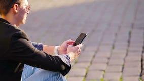 Il primo piano delle mani maschii sta tenendo il cellulare all'aperto sulla via Uomo che per mezzo dello smartphone mobile archivi video