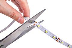 Il primo piano delle mani tiene le forbici che stanno tagliando la striscia del LED Fotografie Stock