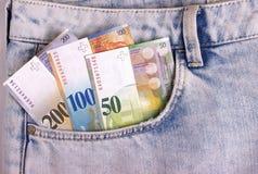 Il primo piano delle note dello svizzero nei jeans intasca Immagini Stock
