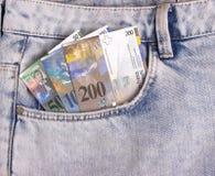 Il primo piano delle note dello svizzero nei jeans intasca Immagine Stock