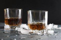 Il primo piano delle paia di ol ha adattato i vetri Brandy e pezzi di ghiaccio sulla tavola grigia contro la parete scura fotografia stock