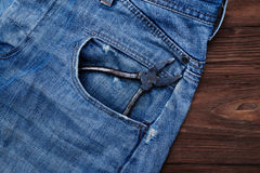 Il primo piano delle pinze in jeans di un denim intasca con un ove dello spazio della copia Fotografia Stock