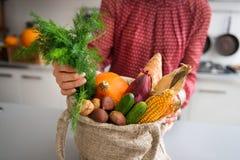 Il primo piano delle verdure e dei dadi di caduta nella borsa di tela da imballaggio ha tenuto dalla donna Immagini Stock Libere da Diritti