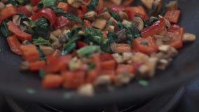 Il primo piano delle verdure rosse del taglio con le erbe sta friggendo in una pentola sulla stufa archivi video