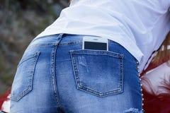Il primo piano dello smartphone, ragazza in denim blu mette la vista in cortocircuito posteriore Fotografia Stock Libera da Diritti