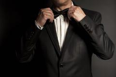 Il primo piano dello smoking d'uso del signore raddrizza la sua cravatta a farfalla fotografie stock