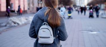 Il primo piano di bella ragazza castana con capelli lunghi in un cappotto gira intorno alla città in primavera, vista da dietro Fotografia Stock Libera da Diritti