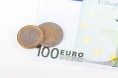 Il primo piano di cento banconota dell'euro e euro conia sulla parte posteriore di bianco Immagine Stock Libera da Diritti