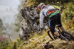 Il primo piano di giovane atleta del cavaliere sulla bici guida su una traccia di montagna fotografia stock