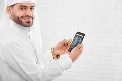 Il primo piano di giovane cryptotrader musulmano tiene il telefono cellulare fotografie stock