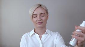 Il primo piano di giovane donna bionda usa uno spruzzo di fissazione di trucco sul suo fronte video d archivio