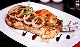 Il primo piano di porco cucinato con le verdure è servito sul piatto bianco Fotografia Stock Libera da Diritti