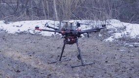 Il primo piano di quadcopter decolla clip Il modello potente del quadcopter della nuova generazione è su terra che prepara per il stock footage