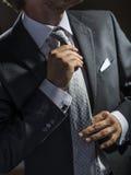 Il primo piano di sharp ha vestito l'uomo d'affari che regola la sua cravatta Fotografia Stock