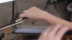 Il primo piano di un arco con le serie di violoncello, violoncellista professionista gioca video d archivio
