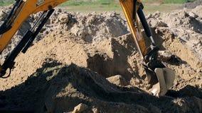 Il primo piano di un escavatore del secchio solleva la terra Concetto di costruzione archivi video
