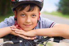 Il primo piano di un ragazzo dell'adolescente in casco protettivo che si siede sulla sua bicicletta e tiene la sua testa sulle su fotografia stock