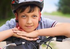 Il primo piano di un ragazzo dell'adolescente in casco protettivo che si siede sulla sua bicicletta e tiene la sua testa sulle su fotografia stock libera da diritti