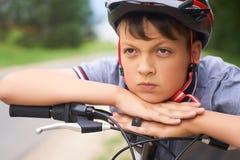 Il primo piano di un ragazzo dell'adolescente in casco protettivo che si siede sulla sua bicicletta e tiene la sua testa sulle su immagini stock libere da diritti